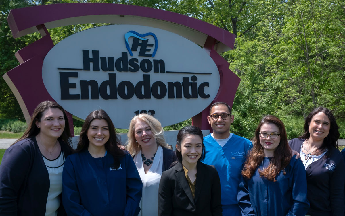 Team members standing in front of the Hudson Endodontic Sign